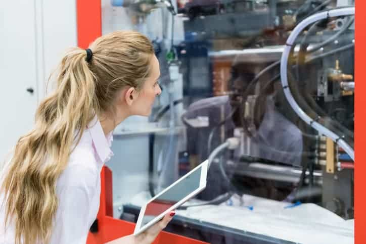 Horizontal color image of woman manager in factory control the production and using digital tablet.