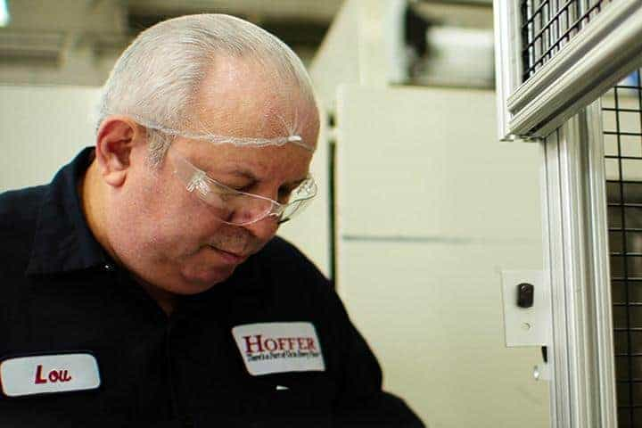 hoffer employee with hair net looking down